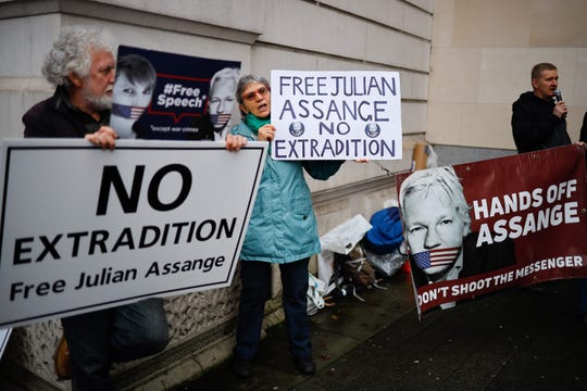 "Supporters of Wikileaks founder Julian Assange hold placards outside Westminster Magistrates Court in London on December 19, 2019. The legal team of WikiLeaks founder Julian Assange's will argue he should not be extradited to the US because his alleged offenses are being framed as ""political"" in nature, a court heard."