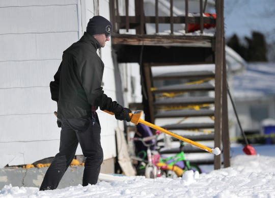 A Kaukauna police officer uses a metal detector to scan the backyard of the Crooks Avenue home where two children were found dead, during an investigation Tuesday, February 18, 2020, in Kaukauna, Wis. William Beyer, 5, and Danielle Beyer, 3, were found dead by police shortly after 7 a.m. inside a home in the 1200 block of Crooks Avenue on Monday, February 17, 2020.
