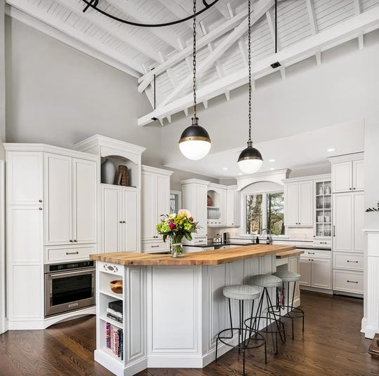 The gourmet kitchen features a double-height ceiling and all white custom cabinetry.