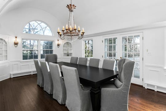 The dining room features French Doors decorative molding and wood flooring.