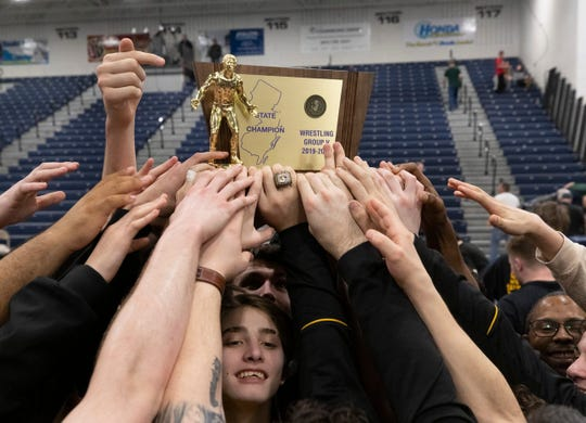 Southern Regional wrestlers celebrate and lift the NJSIAA Group V championship plaque after the Rams' 38-24 win over Manalapan this past Sunday night in the NJSIAA Group V championship match