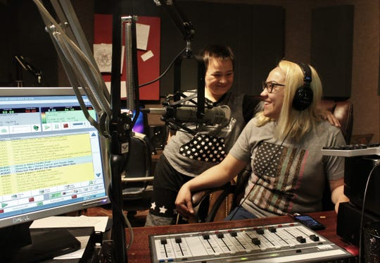Crystal King, right, and her son Sebastian share a laugh before she goes on the air Monday at radio station KVVO. The monitor at the left shows which song is playing and which are coming (in blue). The studio is located in the KGNZ complex on Butternut Street.