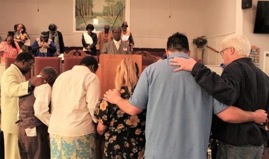 Gary HIll, right, general manager of radio station KGNZ, and others join Henry Flint and KVVO staff in a prayer led by the Rev. Eddie Jordan to dedicate the black gospel station.