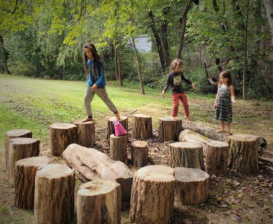 Kids create an obstacle course game with logs at ZigZag, which is hosting summer camps.