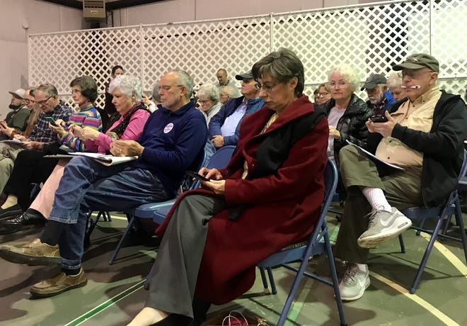 Attendees of a public input session for Black Mountain's 30-year comprehensive plan participate in an online survey on their phones.