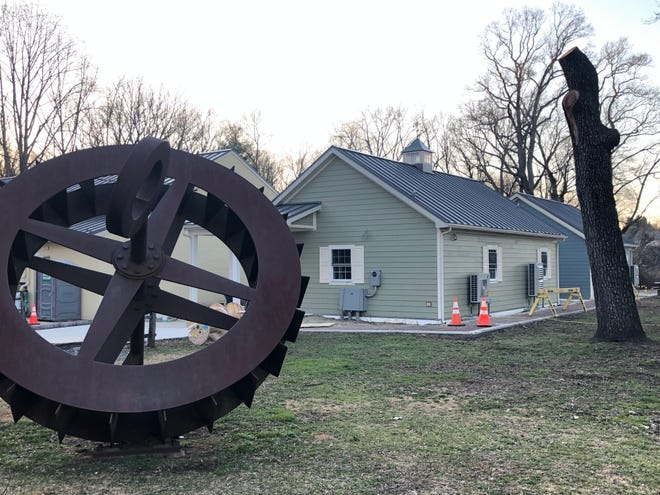 The 'Free Wheel' sculpture, a tribute to Croft Farm's history as a mill, is at the foreground of new classroom buildings constructed on the Cherry Hill site.