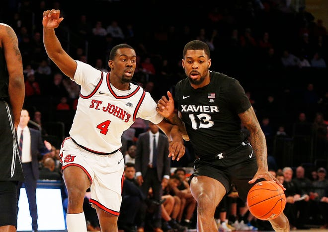 Feb 17, 2020; New York, New York, USA;  Xavier Musketeers forward Naji Marshall (13) dribbles the ball against St. John's Red Storm guard Greg Williams Jr. (4) during the first half at Madison Square Garden.
