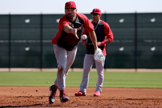 Cincinnati Reds first baseman Joey Votto (19) flips to first base during fielding drills, Tuesday, Feb. 18, 2020, at the baseball team's spring training facility in Goodyear, Ariz.