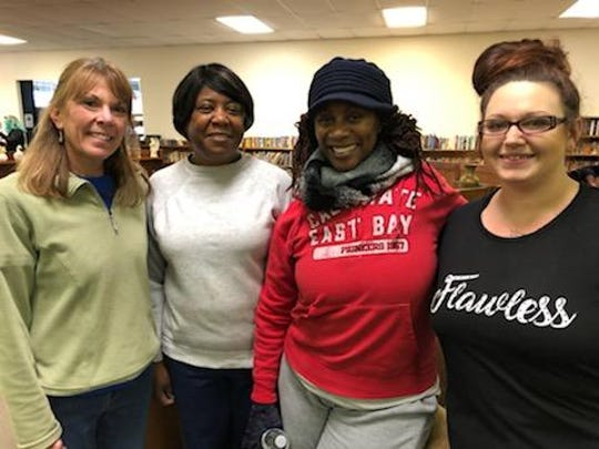 Volunteers and future homeowners work together in the Clarksville ReStore to improve the working space.
