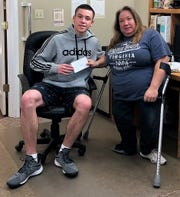 Zach Balo of Coshocton County Youth Leadership presents a $100 check to Candy Angle, president of the Coshocton County Handicapped Society. The organization is dependent on donations and volunteers to help those in the community need.