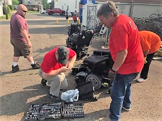 Volunteers with the Coshocton County Handicapped Society work on fixing power scooters. Many items donated are used and need repairs or parts.
