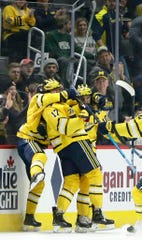 Michigan forward Will Lockwood, right, celebrates with forward Johnny Beecher (17) after scoring against Michigan State on Feb. 17, 2020, in Detroit. The Wolverines beat the Spartans, 4-1, as Lockwood had two goals.