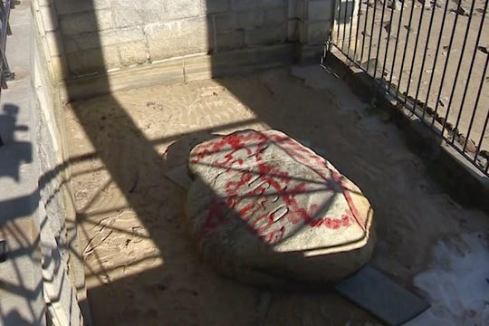 Plymouth Rock and other sites were covered in red graffiti Monday .