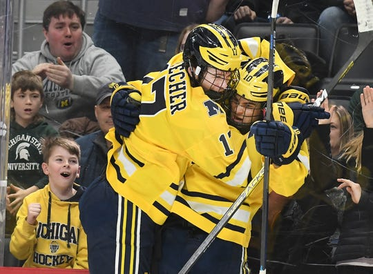 Michigan's Johnny Beecher collides into Will Lockwood after Lockwood's goal in the first period.
