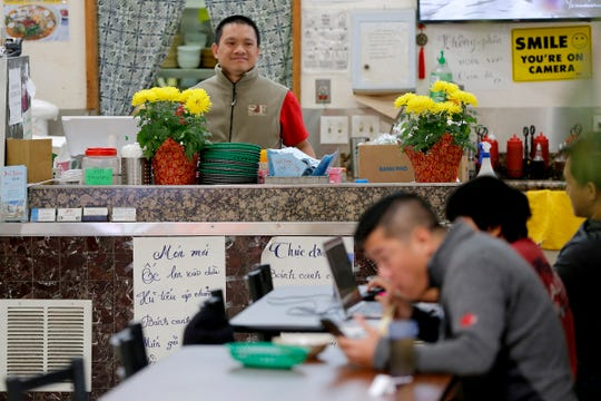 In this Feb. 13, 2020, photo, restaurant owner Phong Nguy watches from his counter as customers eat lunch in the food court at the Mekong Plaza in the Asian district, in Mesa, Ariz.