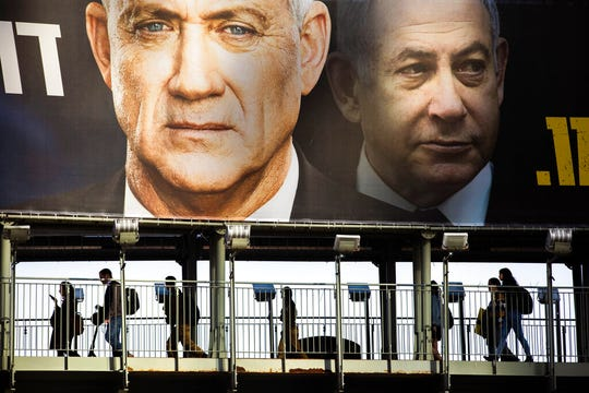 People walk on a bridge under an election campaign billboard of Blue and White party shows its party leader Benny Gantz, and Israeli Prime Minister Benjamin Netanyahu, in Ramat Gan, Israel, Tuesday, Feb. 18, 2020.