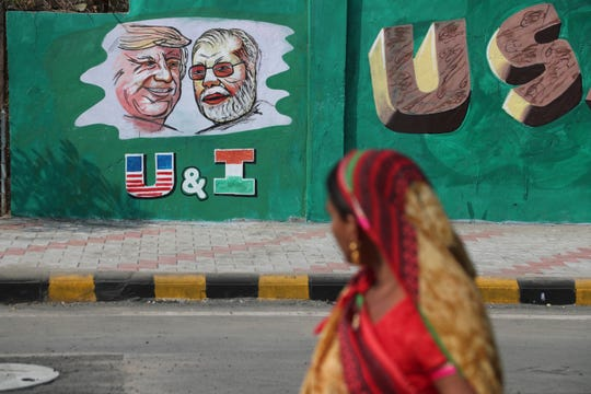 An Indian woman looks at a wall painted with portraits of U.S. President Donald Trump and Indian Prime Minister Narendra Modi ahead of Trump's visit, in Ahmadabad, India.