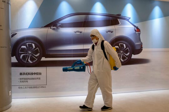 A worker disinfects a mall near an advertisement for a car in Beijing, China, on Feb. 12.