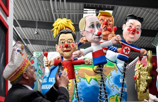 A satiric carnival float depicting the leaders of China, United Kingdom, Russia, USA and North Korea, Xi Jinping, Boris Johnson, Vladimir Putin, Donald Trump and Kim Jong-un as puppets is watched by a reveller during a preview in a hall in Cologne, Germany, Tuesday, Feb. 18, 2020.