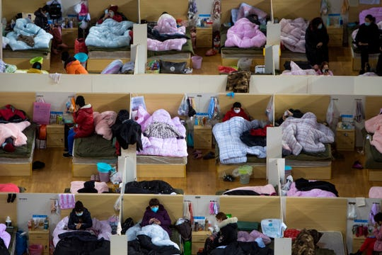In this Monday, Feb. 17, 2020, photo released by Xinhua News Agency, patients infected with the coronavirus take rest at a temporary hospital converted from Wuhan Sports Center in Wuhan in central China's Hubei Province.