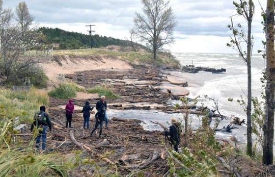 People assess the damage on the beach at Point Betsie Lighthouse, north of Frankfort, on Oct. 16, after gale-force winds on Lake Michigan pushed near-record-high water onto the beach along with a huge amount of woody debris.