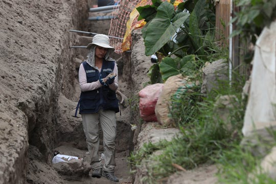 In this Feb. 12, 2020 photo, an archaeologist stands next to ancient bones and vessels from a previous Inca culture that were discovered by workers building a new natural gas line through the Puente Piedra neighborhood of Lima, Peru.