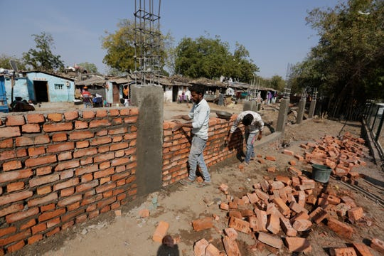Indian workers construct a wall in front of a slum ahead of U.S. President Donald Trump's visit, in Ahmadabad, India, Monday, Feb. 17, 2020. Trump is scheduled to visit the city during his Feb. 24-25 India trip.