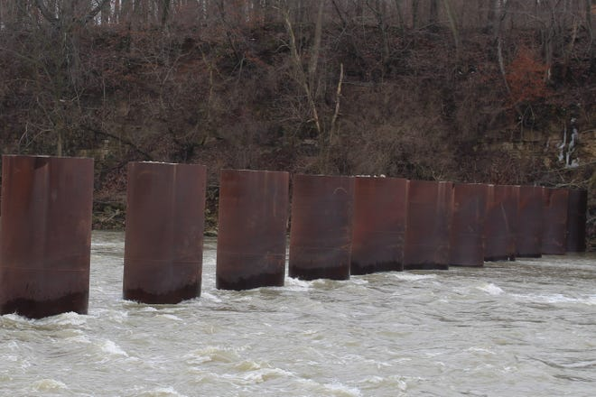 The Sandusky River flows through the city's ice control structure near the former Ballville Dam site Tuesday. The city has had discussions with the U.S. Army Corps of Engineers about possibly removing some of the pillars in the structure, which has 15 pillars about 200 feet downstream from the former dam site. The pillars are 21 feet apart, six feet in diameter, and rise 15 feet above the river's normal water level.
