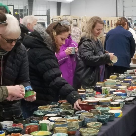 Guests look over soup bowls made mostly by local students to purchase at last year's ZoupArt. The annual soup lunch and fundraiser for Bruemmer Park Zoo in Kewaunee takes place Sunday.