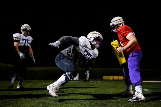 Furman's Bo McKinney (77), middle, runs through drills with his teammates during practice at Paladin Stadium Tuesday, Feb. 18, 2020.