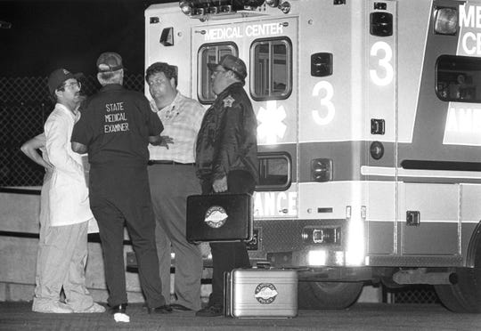 An ambulance carrying bodies from the Pyro coal mine disaster stands outside the Madisonville medical center. Left to right were Dr. Mark LeVaughn, forensic pathologist with the Western Kentucky Forensic Center, David Jones, administrator for the state medical examiner's office, Charles O'Nan, Hopkins County deputy coroner, and Bruce Farmer, who at that time was a Henderson County deputy coroner.