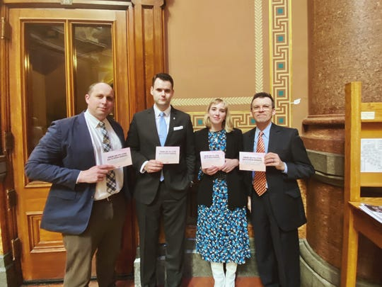 "Dr. Daniel Runde, Sen. Zach Wahls, IHRC Executive Director Sarah Ziegenhorn and Sen. Joe Bolkcom at the Iowa State Capitol Feb. 11, 2020, in Des Moines. The cards they hold read, ""Iowans are still dying due to opioid overdose."""