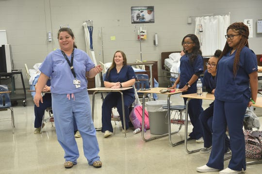 Dr. Felicitas Koller (left) leads a training session for Brookhaven High School students on how to stop bleeding.