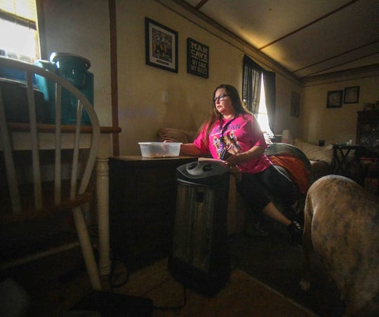 Ashley Jennings, a Harbor Pines resident, sits in her home with her dog Tigerpuss for the first time in a week after residents were forced to evacuate their home due to flood waters from the Pearl River in Ridgeland, Miss. Tuesday, Feb. 18, 2020.