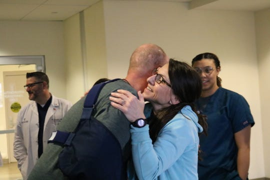 Wade Berzas, left, hugs Our Lady of Lourdes team members before leaving the hospital on Feb. 17. Berzas was the lone survivor of a December plane crash in Lafayette that left five others dead.