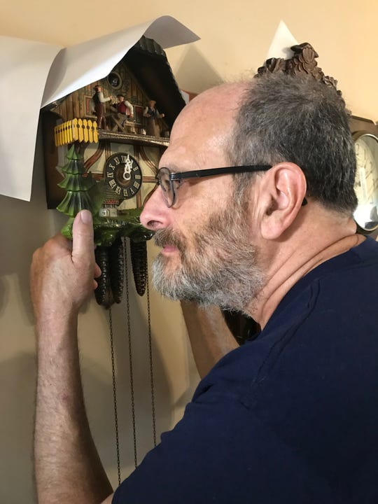 Lancaster Eagle-Gazette columnist Mark Kinsler recently won an Associated Press writing award and is releasing a new book of his columns. In addition to writing, Kinsler also repairs clocks like this coo-coo clock he is examining.