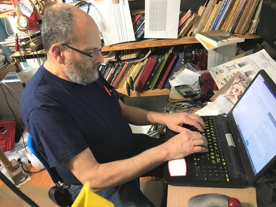 Mark Kinsler writes his Lancaster Eagle-Gazette columns in the corner of his clock repair shop in his house. Kinsler recently released a book comprised of his columns, his second such book since 2014.