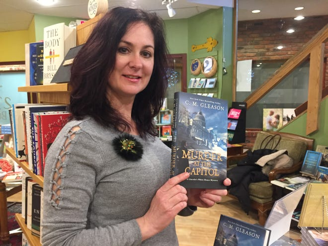 "Brighton Township author Colleen Gleason holds a copy of her newest novel, ""Murder at the Capitol,"" Tuesday, Feb. 18, 2020, at 2 Dandelions Bookshop in Brighton."