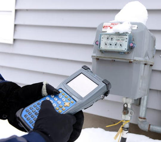 A Consumers Energy employee reads a gas meter in 2014.