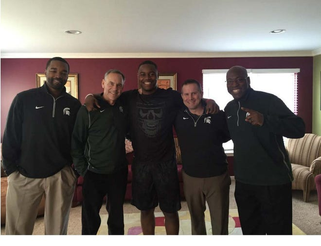 From left, Curtis Blackwell II, former MSU football coach Mark Dantonio, potential recruit Daelin Hayes, assistant coach Mike Tressel and assistant coach Harlon Barnett in Hayes' home on Dec. 7, 2015. Blackwell, who is suing Dantonio and other university officials, says the photo proves Dantonio violated NCAA rules.