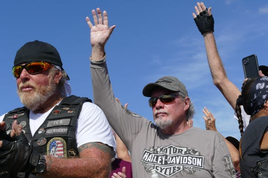 Vietnam war veterans raise their hand at the I-75 rest stop by exit 131 as hundreds of bikers set to escort The Wall That Heals from Fort Myers to Marco Island on Feb. 18, 2020.