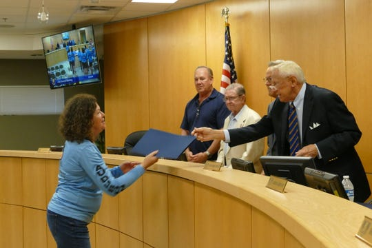 Chairperson Erik Brechnitz of the Marco Island City Council hands a proclamation to Lori Beall, membership director of the Owl Watch program, on Feb. 18, 2020.