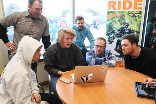 From left, Adan Davis-Quiroz, 16, a sophomore, Bjorn Christensen, a mentor and engineer from Harley-Davidson, Jack Gennerman, 16, a junior, Alfonso Callejo, a mentor and an engineer from Harley-Davidson, Kasey Peck, a mentor and engineer from Harley-Davidson, and Philip Birschbach, a mentor and engineer from Harley-Davidson, work on hashing out the features and changes they want on the project bike they are customizing.