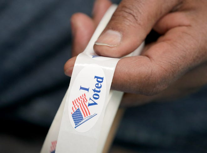 """Poll worker Charles Hawkins holds """"I Voted"""" stickers at the Mary Ryan Boys & Girls Club of Greater Milwaukee on North Sherman Boulevard in Milwaukee on Tuesday, Feb. 18, 2020."""