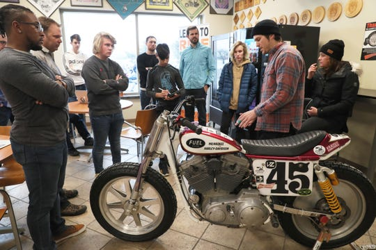 Racer J.J. Flairty, right, explains to Kettle Moraine High School students and their mentors how he modified his personal flat track racing bike for the sport. Royal Enfield is partnering with area schools to teach students how to build motorcycles.