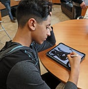 Kabir Jeevraj, 14, a freshman, works on his tablet to come up with a drawing of how the project motorcycle might look when it's finished.