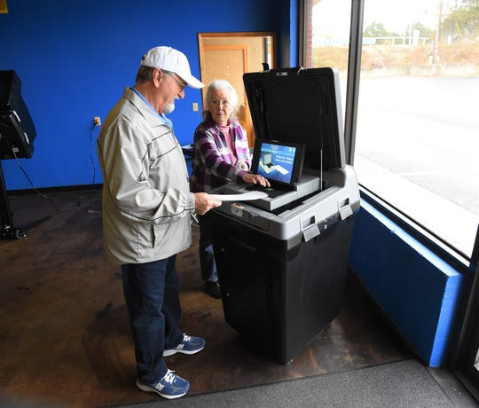 Poll worker Linda Hewtt helps James Maycunich feed his paper ballot into the tabulator Tuesday at the Twin Lakes Plaza voting center. Early voting for the March 3 primary election opened statewide Tuesday and continues through March 2.