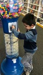 Juan Perez, 4, watches a giant gumball spiral through the Gumball Wizard.