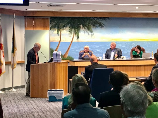 A stack of nearly 2,500 petitions in opposition to bike lanes on Gulf Shore Boulevard, residents said, sits on the podium as people speak before the Naples City Council at a public workshop on Tuesday, Feb. 18, 2020.