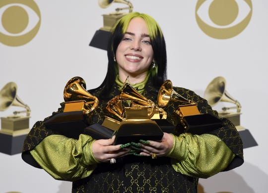 "Billie Eilish poses in the press room with the awards for best album and best pop vocal album for ""We All Fall Asleep, Where Do We Go?"" best song and record for ""Bad Guy"" and best new artist at the 62nd annual Grammy Awards earlier this year in Los Angeles."
